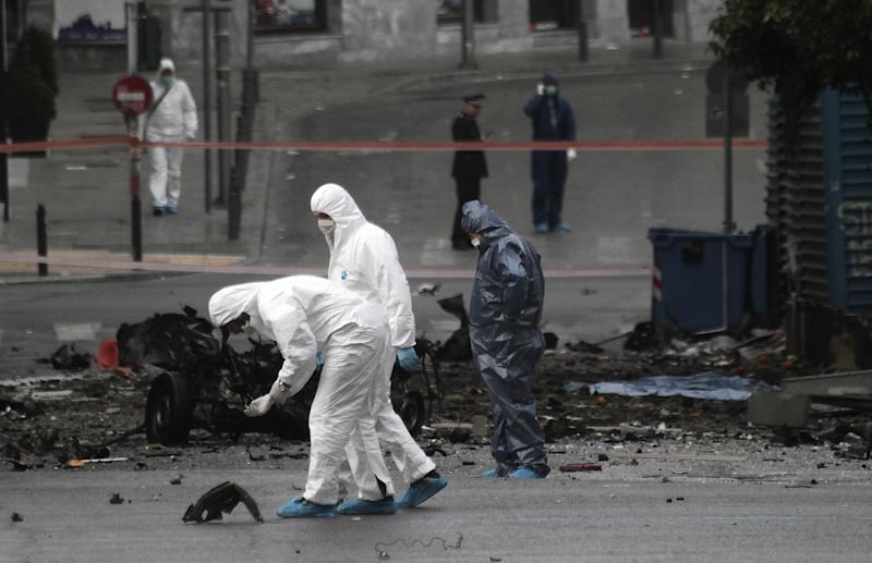 Police bomb disposal experts search for evidence next to remains of a car after a car bomb explosion in central Athens on Thursday, April 10, 2014. A bomb exploded outside a Bank of Greece building in central Athens before dawn Thursday, causing some damage but no injuries. The blast came hours before Greece was to return to the international bond markets for the first time in four years, and a day before German Chancellor Angela Merkel was to visit Athens.(AP Photo/Dimitri Messinis)