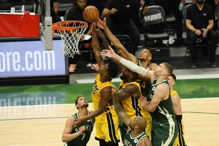 Miami Heat star Jimmy Butler (22) shoots under pressure from Milwaukee Bucks players in their playoff series opener