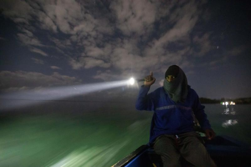 White River Fish Sanctuary warden Mark Lobban shines a spotlight on the protected reef while patrolling the no-take zone for illegal fishermen under moonlight in Ocho Rios, Jamaica, Friday, Feb. 15, 2019. Most of the older and more established fishermen, who own boats and set out lines and wire cages, have come to accept the no-fishing zone. Some younger men though, some of them poor and with few options, are the most likely trespassers. (AP Photo/David Goldman)