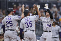 Colorado Rockies' Ryan McMahon, right, celebrates with Elias Diaz (35) and C.J. Cron (25) after hitting a grand slam against the San Diego Padres during the first inning of a baseball game Friday, July 30, 2021, in San Diego. (AP Photo/Derrick Tuskan)