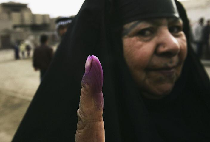 <p>A woman displays her ink-stained finger outside a polling station after voting on Election Day in the Sadr City neighborhood of Baghdad January 30, 2005 in Baghdad, Iraq. Iraq 's first multiparty elections in half a century began at 7am on Sunday. (Photo by Chris Hondros/Getty Images) </p>