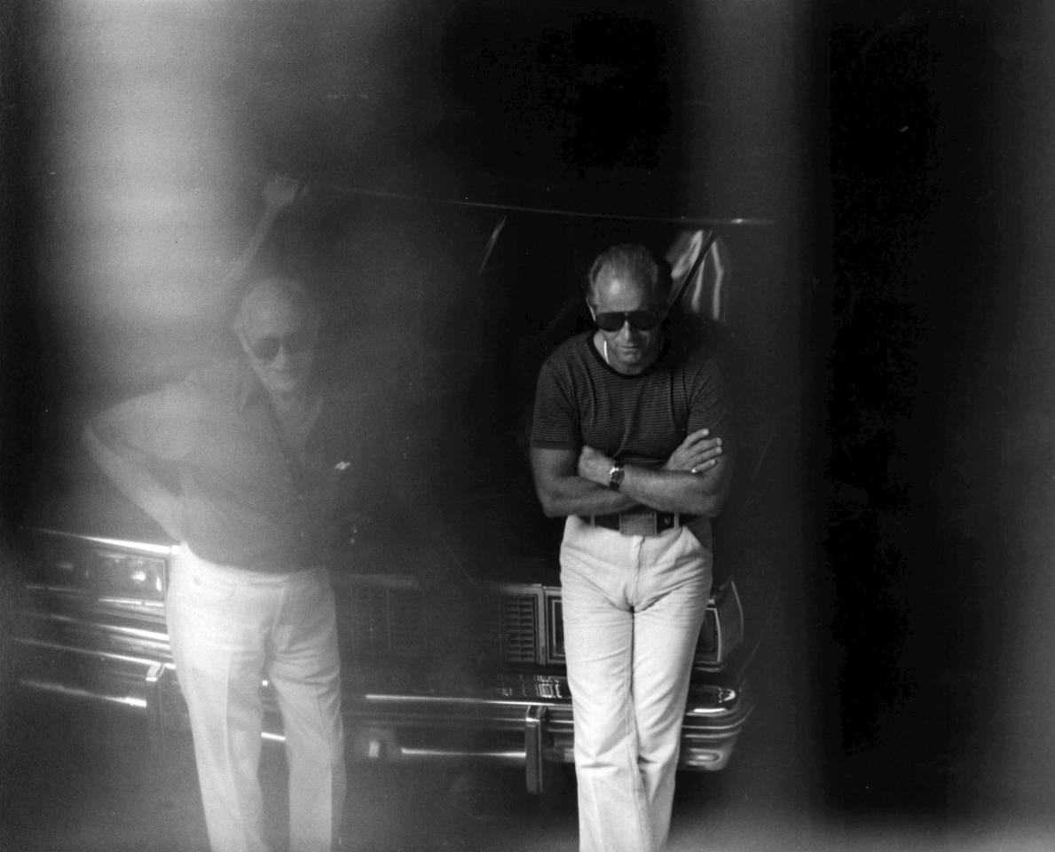 """This 1980 black and white surveillance photo released by the U.S. Attorney's Office and presented as evidence during the first day of a trial for James """"Whitey"""" Bulger in U.S. District Court in Boston, Wednesday, June 12, 2013, shows Bulger, right, with another man at a Lancaster Street garage in Boston's North End. Bulger is on trial for a long list of crimes, including extortion and playing a role in 19 killings. (AP PhotoU.S. Attorney's Office)"""