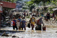 Residents walk on mud and debris as they retrieve belongings from their homes at the typhoon-damaged Kasiglahan village in Rodriguez, Rizal province, Philippines on Friday, Nov. 13, 2020. Thick mud and debris coated many villages around the Philippine capital Friday after Typhoon Vamco caused extensive flooding that sent residents fleeing to their roofs and killing dozens of people. (AP Photo/Aaron Favila)