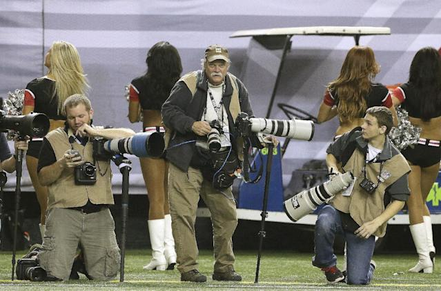 In this Sunday, Dec. 29, 2013, photo, AP Photographer Dave Martin, second from right, works during the first half of an NFL football game between the Carolina Panthers and the Atlanta Falcons, in Atlanta. Martin, a longtime Associated Press photographer based in Montgomery, Ala., died after collapsing on the Georgia Dome field at the Chick-fil-A Bowl on Tuesday, Dec. 31, 2013. Martin was 59. (AP Photo/John Bazemore)