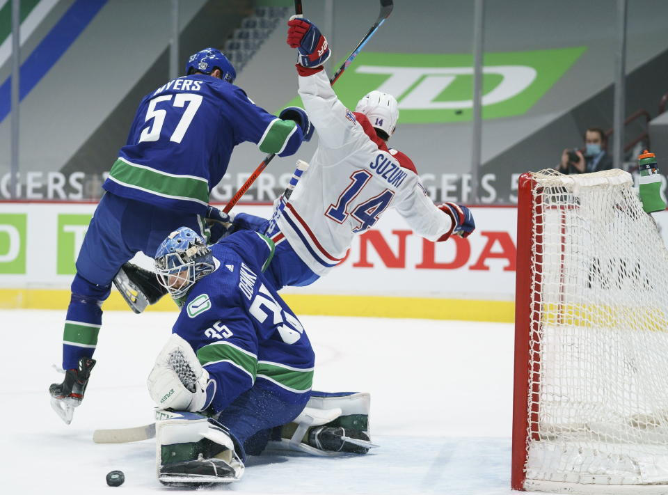 Vancouver Canucks defenseman Tyler Myers (57) clears Montreal Canadiens centre Nick Suzuki (14) away from Canucks goaltender Thatcher Demko (35) during the first period of an NHL hockey game Thursday, Jan. 21, 2021, in Vancouver, British Columbia. (Jonathan Hayward/The Canadian Press via AP)