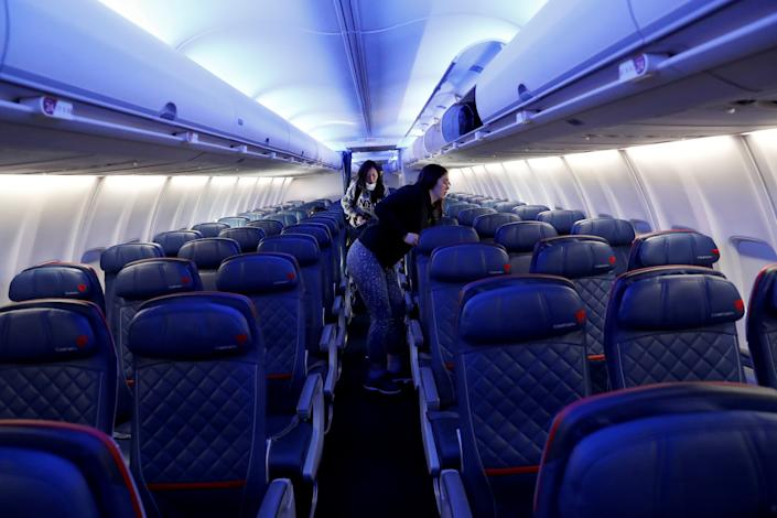 Air travelers grab carry-on luggage behind rows of empty seats aboard a Delta flight, as coronavirus disruption continues across the global industry, from New York's JFK International Airport to San Francisco, California, U.S., March 17, 2020.