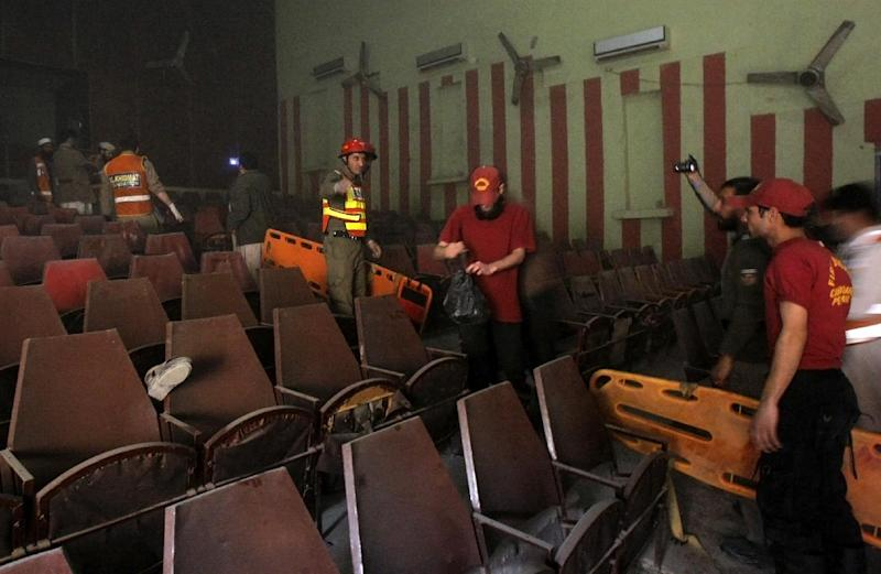 "Pakistani rescue workers examine the site of a grenade attack on a crowded movie theater that killed and wounded many people in Peshawar, Pakistan, Tuesday, Feb. 11, 2014. About 80 people were watching a movie called ""Yarana,"" which means friendship in Pashto, said an official. No one immediately claimed responsibility for the attacks, which come days after Pakistan began a peace process with Taliban militants fighting in the country's northwest to end the violence that has killed more than 40,000 people in recent years. (AP Photo/Mohammad Sajjad)"