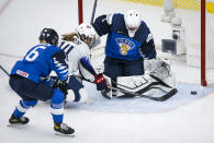Finland goalie Anni Keisala, right, blocks a shot from Brianna Decker, center, of the United States, as Finland's Petra Nieminen checks Decker during the first period of an IIHF women's hockey championships semifinal in Calgary, Alberta, Monday, Aug. 30, 2021. (Jeff McIntosh/The Canadian Press via AP)