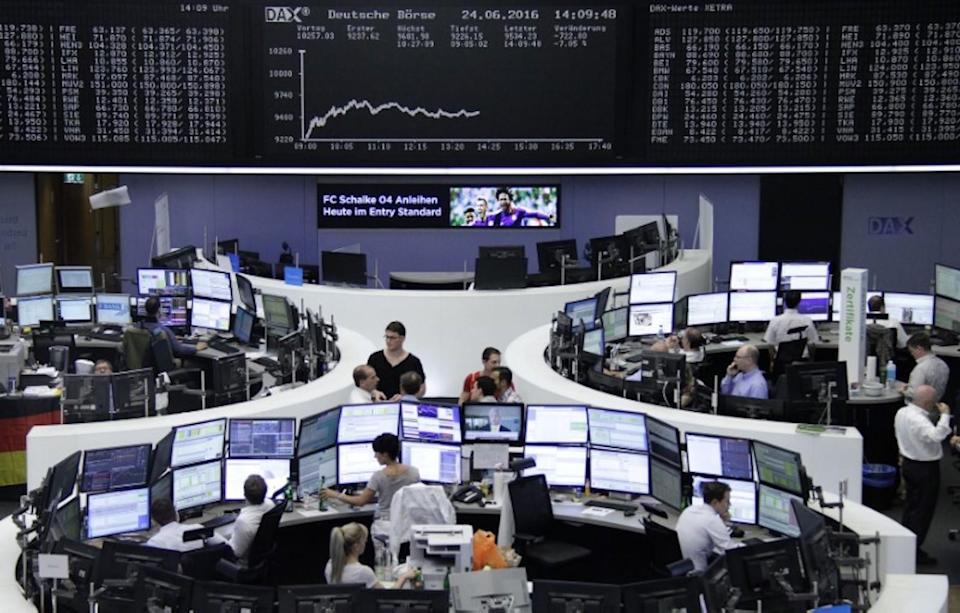 Traders work at their desks in front of the German share price index, DAX board, at the stock exchange in Frankfurt, Germany. Photo: Reuters