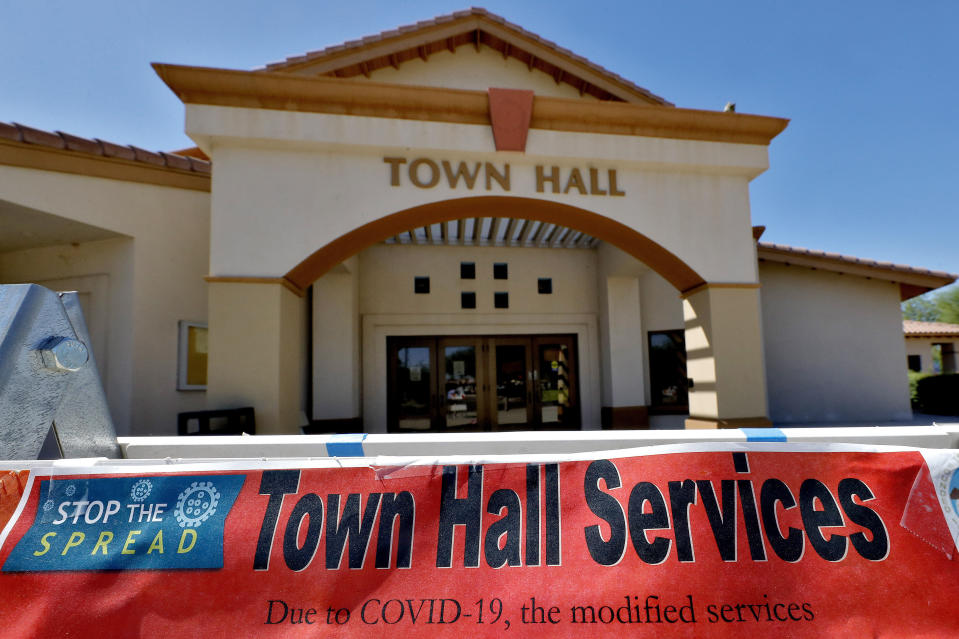 In this Thursday, June 18, 2020, photo, a sign in front of the Guadalupe Town Hall notifies visitors of modified services in Guadalupe, Ariz. As the coronavirus spreads deeper across America, it's ravaging through the homes and communities of Latinos from the suburbs of the nation's capital to the farm fields of Florida to the sprawling suburbs of Phoenix and countless communities in between. (AP Photo/Matt York)