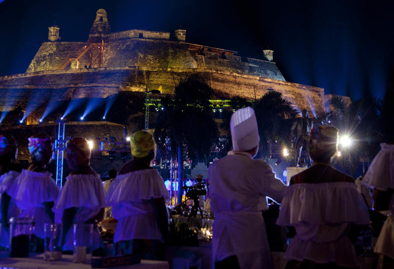 Servers line the buffet outside the San Felipe castle where leaders attend a dinner during the sixth Summit of the Americas in Cartagena, Colombia, Friday April 13, 2012. (AP Photo/Carolyn Kaster)