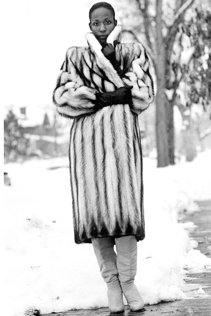<p>A woman wears a fur coat and slouchy leather boots out in the snow. </p>
