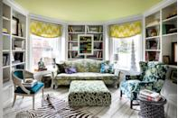 """<p>Take your cues from the bold pattern mixing and modern artwork on display in this living room designed by <a href=""""https://www.ensembliers.com/"""" rel=""""nofollow noopener"""" target=""""_blank"""" data-ylk=""""slk:Les Ensembliers"""" class=""""link rapid-noclick-resp"""">Les Ensembliers</a>. A light green color on the ceiling is an unexpected surprise that can tie the whole room together. Here, it pairs beautifully with the yellow curtains, geometric green ottoman, and plenty of gray tones throughout. </p>"""