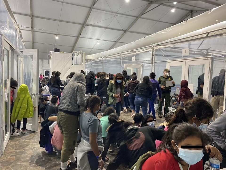 This photo released on March 22, 2021 by the office of Rep. Henry Cuellar, D-Texas shows migrants crowded in a room with walls of plastic sheeting at the U.S. Customs and Border Protection temporary processing center in Donna, Texas. (Handout via Reuters)