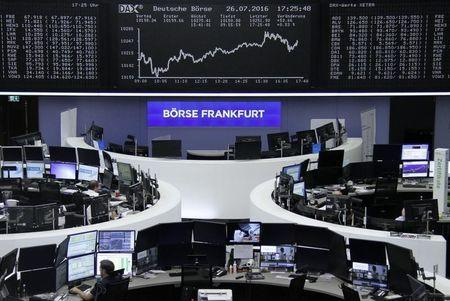 Traders work at their desks in front of the German share price index, DAX board, at the stock exchange in Frankfurt, Germany, July 26, 2016. REUTERS/Staff/Remote