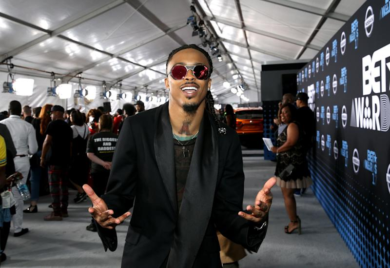August Alsina looks fly in black suit, with red shades and he looks good-looking