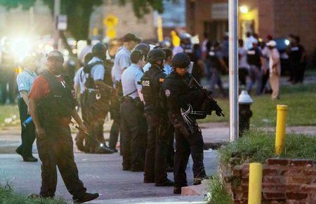Police line up to block the street as protesters gathered after a shooting incident in St. Louis, Missouri August 19, 2015. REUTERS/Kenny Bahr