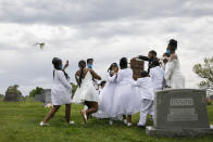 Grandchildren of Joanne Paylor, of southwest Washington, react to doves as they are released by Compassion and Serenity Funeral Home Administrator Dani Skinner, during the interment ceremony for Paylor at Lincoln Memorial Cemetery in Suitland-Silver Hill, Md., Sunday, May 3, 2020. The family delayed Paylor's funeral for almost two months hoping the social distancing rules would be lifted. Despite not having died from coronavirus, almost every aspect of her funeral has been impacted by the pandemic. (AP Photo/Jacquelyn Martin)
