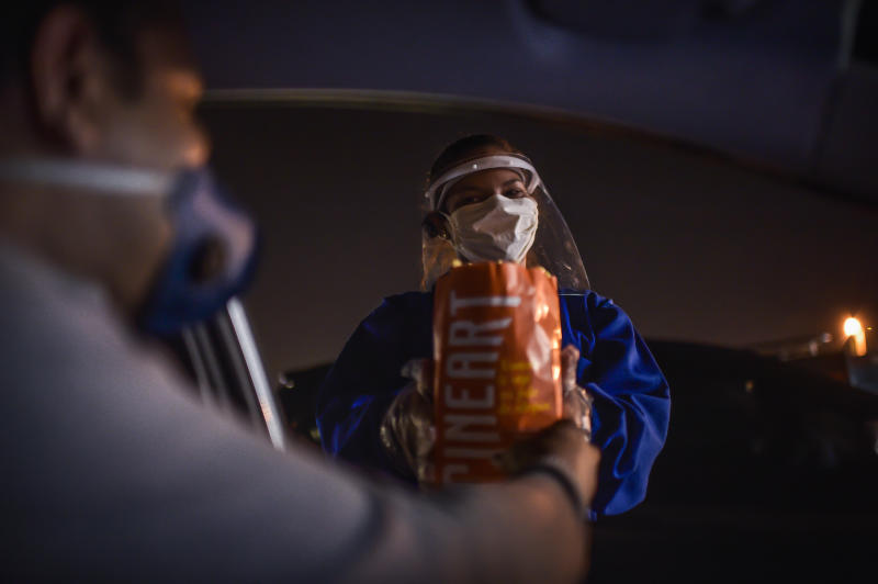 BELO HORIZONTE, BRAZIL - JUNE 14: Employee delivers popcorn out of a car window at Cine Drive-In on May 22, 2020 in Belo Horizonte, Brazil. The closed movie theaters, the drive-in cinema starts to be an option of entertainment in amid the coronavirus pandemic (COVID - 19). (Photo by Pedro Vilela/Getty Images)