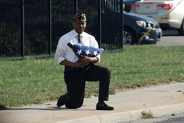 <p>SEPT. 27, 2017 – U.S. Army veteran Marvin Boatright kneels with a folded U.S. flag as the motorcade of President Donald Trump passes him after an event at the state fairgrounds in Indianapolis, Indiana. This was soon after President Donald Trump had made comments condemning NFL players who kneel during the national anthem. Boatwright said that he wanted to send a message against social injustice. (Photo: Jonathan Ernst/Reuters) </p>