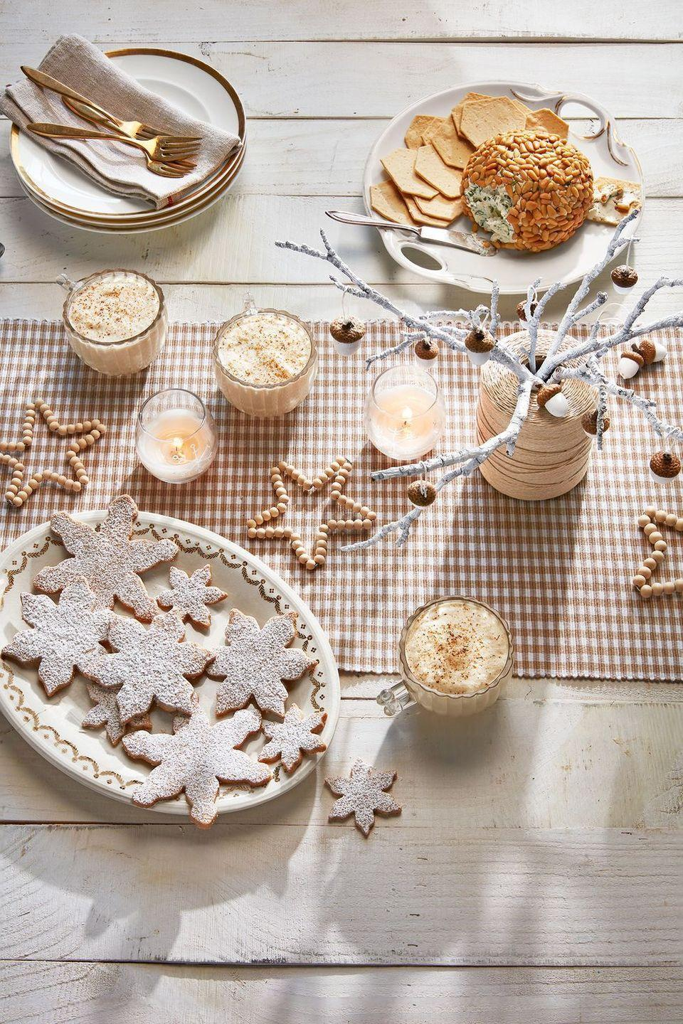 <p>Forget red and green — this understated tablescape relies on muted tones, beaded decorations, and natural beauty (think: twigs and acorns).</p>