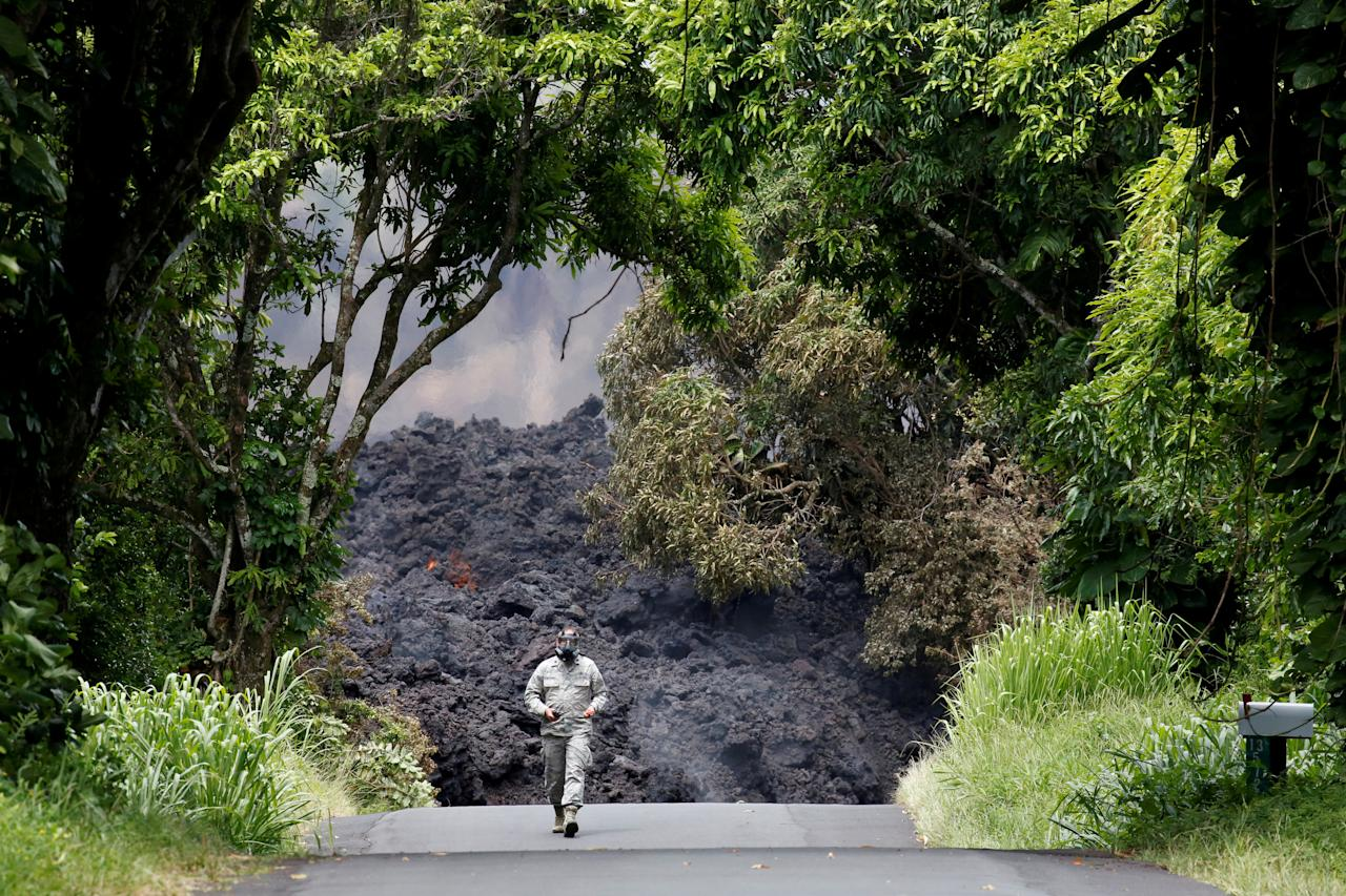 Lieutenant Colonel Charles Anthony, of the Hawaii National Guard, measures sulfur dioxide gas levels at a lava flow on Highway 137 southeast of Pahoa during ongoing eruptions of the Kilauea Volcano in Hawaii, U.S., May 20, 2018.  REUTERS/Terray Sylvester     TPX IMAGES OF THE DAY