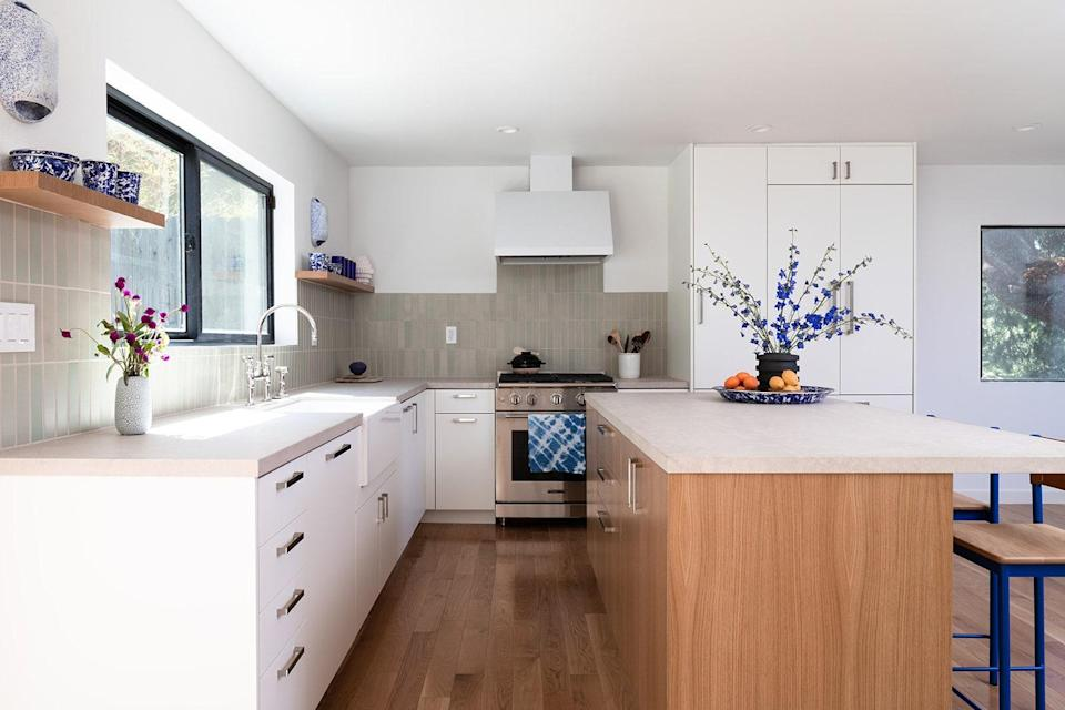 AFTER: Instead of wooden cabinetry on wood floors, which was an initial idea, the white cabinets are now seamless. They're also affordable as they're prefabricated with laminate fronts.