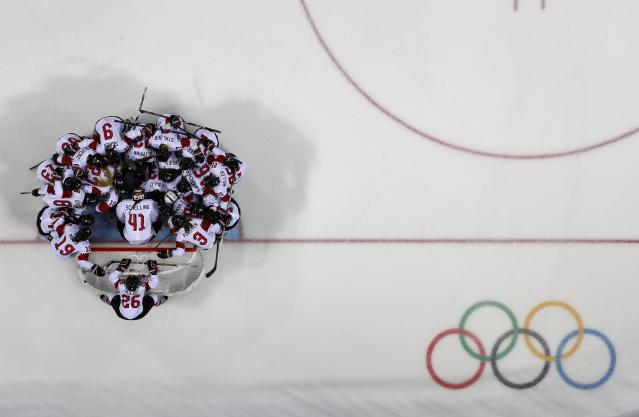<p>Switzerland team gathers on the ice before their game against Sweden. REUTERS/Brian Snyder </p>