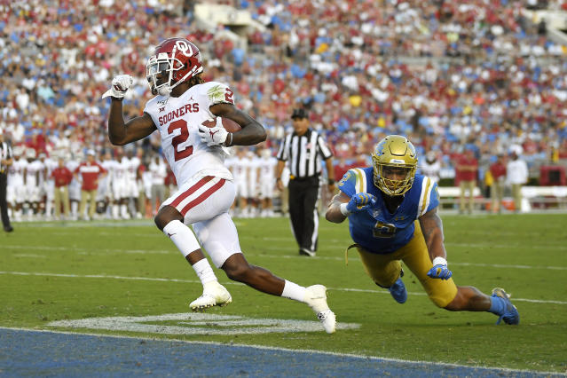 Oklahoma wide receiver CeeDee Lamb, left, runs in for a touchdown as UCLA linebacker Josh Woods defends during the first half of an NCAA college football game Saturday, Sept. 14, 2019, in Pasadena, Calif. (AP Photo/Mark J. Terrill)