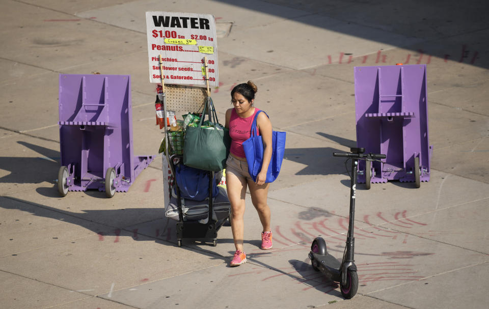 As temperatures soar above triple digits, a vendor pulls a wagon filled with water outside Coors Field during afternoon rush hour Tuesday, June 15, 2021, in Denver. (AP Photo/David Zalubowski)