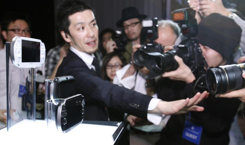 """A Sony Computer Entertainment staff tries to control photographers taking photos of the new PlayStation Portable """"NGP"""" at PlayStation Meeting 2011 in Tokyo Thursday, Jan. 27, 2011. Sony says an upgraded version of its PlayStation Portable machine will go on sale late this year. (AP Photo/Shizuo Kambayashi)"""