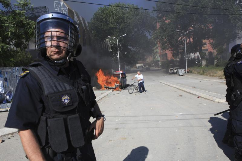 Police stand near a burning vehicle set on fire by Kosovo Albanians during a protest in the ethnically divided town of Mitrovica