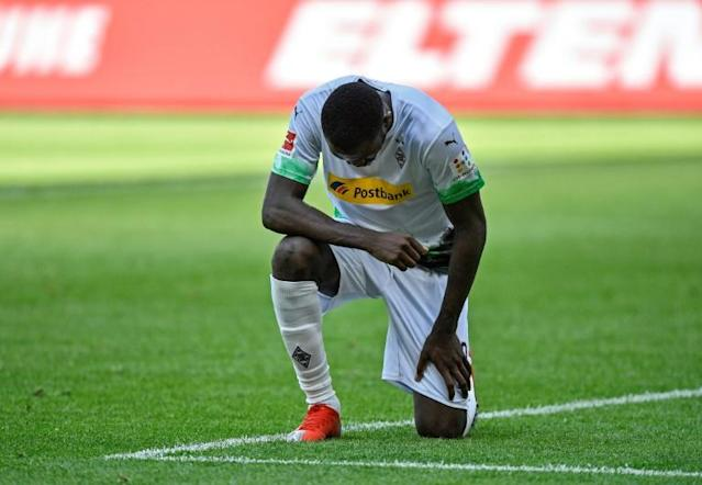 Moenchengladbach forward Marcus Thuram takes a knee after scoring in the Bundesliga, joining the protests over the killing of George Floyd. (AFP Photo/Martin Meissner)