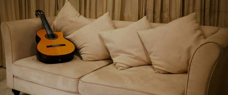 A guitar resting on a sofa in the living room after being used in a recording