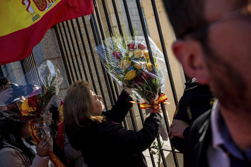 Supporters of late dictator Gen. Francisco Franco place flowers outside Mingorrubio's cemetery, outskirts of Madrid, Thursday, Oct. 24, 2019. Spain has exhumed the remains of Spanish dictator Gen. Francisco Franco from his grandiose mausoleum outside Madrid and flown them by helicopter for reburial in a small family crypt north of the capital. The government-ordered, closed-door operation on Thursday satisfies a decades-old desire of many in Spain who considered the vainglorious mausoleum that Franco built an affront to the tens of thousands who died in Spain's Civil War and his subsequent regime as well as to Spain's standing as a modern democratic state. (AP Photo/Bernat Armangue)