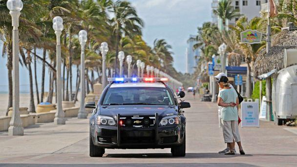 PHOTO: Hollywood Beach Police talk with visitors at Hollywood Boardwalk, which is one of the many places that are not open to the public due to coronavirus, March 18, 2020, in Hollywood, Fla. (David Santiago/Miami Herald via AP)