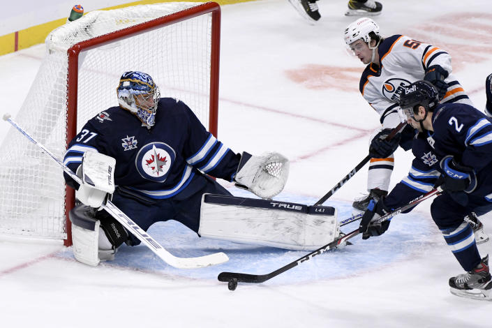 Winnipeg Jets' Dylan DeMelo (2) clears the puck in front of goaltender Connor Hellebuyck (37) after a shot by Edmonton Oilers' Kailer Yamamoto (56) during the second period of an NHL hockey game Tuesday, Jan. 26, 2021, in Winnipeg, Manitoba. (Fred Greenslade/The Canadian Press via AP)
