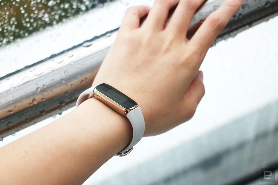 <p>The Fitbit Luxe with a light pink silicone band on a wrist leaning on a wet railing. The screen is off.</p>