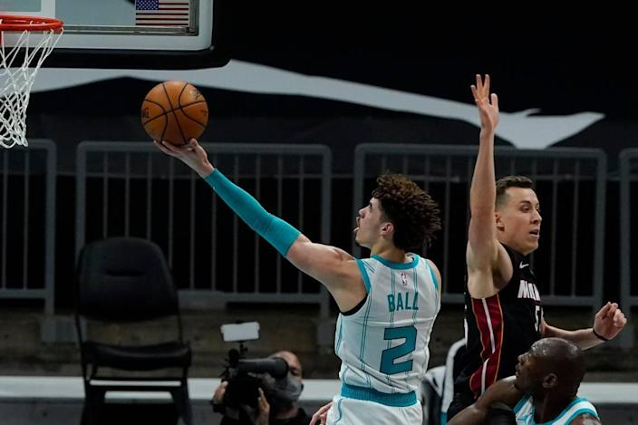 Charlotte Hornets guard LaMelo Ball drives to the basket past Miami Heat Sunday. On the play, Ball switched hands in midair for a left-handed layup.