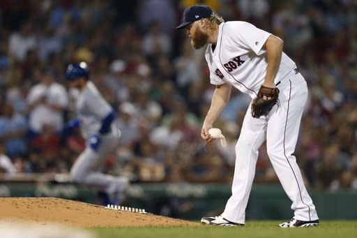 Boston Red Sox's Andrew Cashner picks up the rosin bag after giving up a solo home run to Toronto Blue Jays' Justin Smoak, left, during the sixth inning of a baseball game in Boston, Tuesday, July 16, 2019. (AP Photo/Michael Dwyer)
