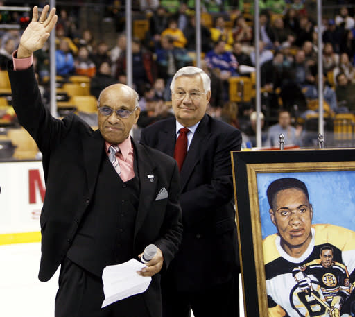 FILE - In this Jan. 19, 2008, file photo, former Boston Bruins hockey player Willie O'Ree waves to the crowd in Boston after being honored on the 50th anniversary of breaking the color barrier in the NHL after the first period of the Bruins hockey game against the New York Rangers in Boston. Looking on is Bruins legend John Bucyk. The Boston Bruins say they are retiring the jersey of Willie ORee, who broke the NHLs color barrier. ORee will have his jersey honored prior to the Bruins Feb. 18 game against the New Jersey Devils. He became the leagues first Black player when he suited up for Boston on Jan. 18, 1958 against the Montreal Canadiens, despite being legally blind in one eye.(AP Photo/Winslow Townson, File)