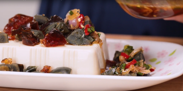 Spread the century eggs over the tofu and drizzle the sauce over it