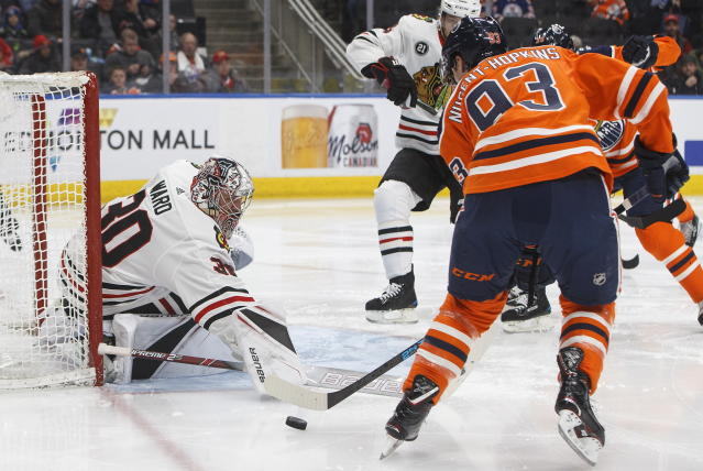 Chicago Blackhawks' goalie Cam Ward (30) makes a save on Edmonton Oilers' Ryan Nugent-Hopkins (93) during the second period of an NHL hockey game Tuesday, Feb. 5, 2019, in Edmonton, Alberta. (Jason Franson/The Canadian Press via AP)