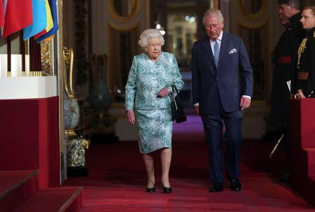 Britain's Queen Elizabeth and Prince Charles arrive for the formal opening of the Commonwealth Heads of Government Meeting in the ballroom at Buckingham Palace in London