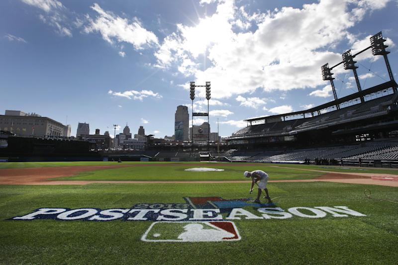 Kyle Pickens paints a postseason logo on the field at Comerica Park before practice for Game 3 of the American League baseball championship series between the Detroit Tigers and Boston Red Sox in Detroit, Monday, Oct. 14, 2013. (AP Photo/Paul Sancya)