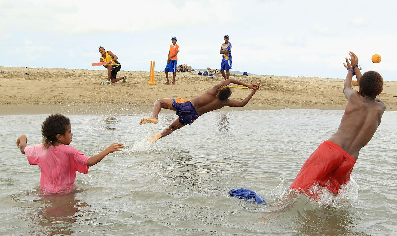 PORT VILA, VANUATU - MAY 16:  Local children catch in the water during an ICC Cricket Development Program Clinic on Mele Beach on May 16, 2012 in Port Vila, Vanuatu.  (Photo by Hamish Blair/Getty Images)