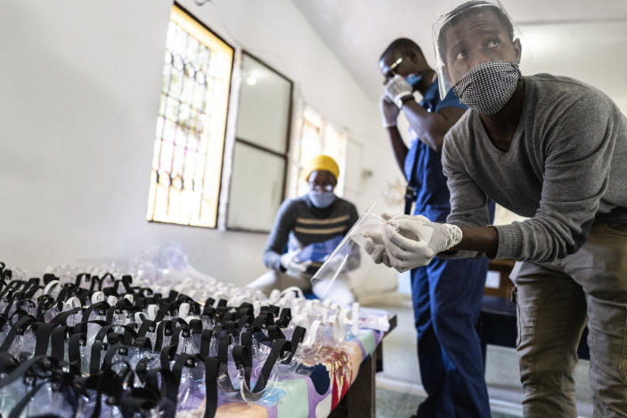 In this photo taken Thursday, April 16, 2020, Idrissa Sall, right, and Mohamed Gueye, second from right, show protective face shields made with a laser cutter, to be used to protect against transmission of the coronavirus, at the FabLab workshop at the Ker Thiossane multimedia center in Dakar, Senegal. Researchers across Africa are looking for ways to make their own ventilators, protective equipment and hand sanitizers as the continent faces a peak in coronavirus cases long after the United States and European countries have bought up global supplies during the pandemic. (AP Photo/Sylvain Cherkaoui)