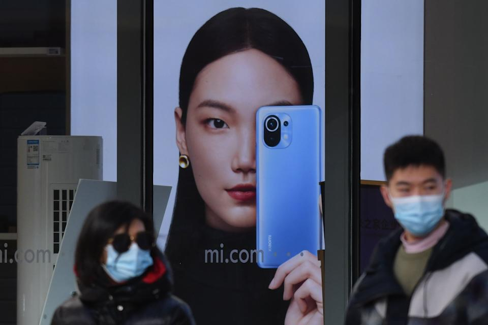 People walk past a Xiaomi store in Beijing on January 15, 2021, as shares in the company collapsed on January 15 after the United States blacklisted the smartphone giant and a host of other Chinese firms. (Photo by GREG BAKER / AFP) (Photo by GREG BAKER/AFP via Getty Images)