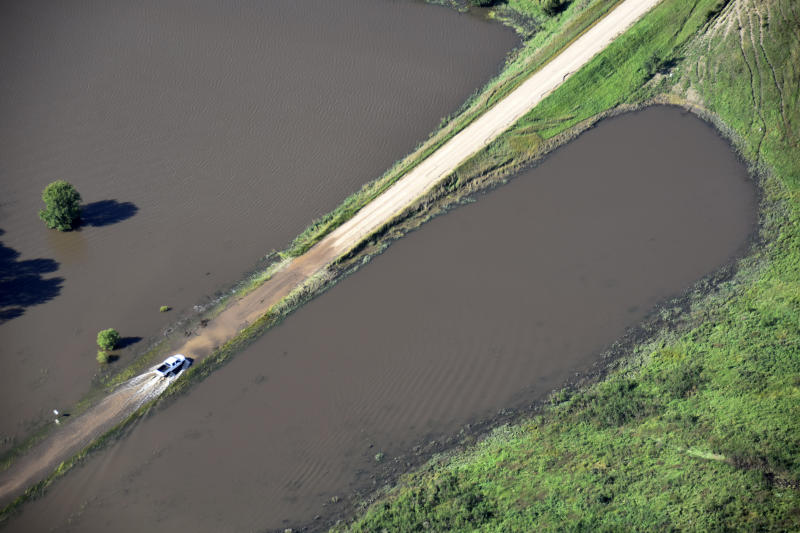 This Saturday, Sept. 14, 2019, aerial photo provided by the South Dakota Civil Air Patrol shows a pickup truck traveling on a partially flooded road in South Dakota's Rosedale Township. (South Dakota Civil Air Patrol via AP)