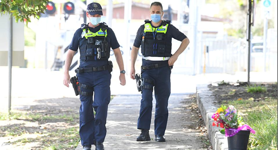 Victoria Police walk past flowers at the scene where a man was stabbed near Seaford Train station in Melbourne, Thursday. Source: AAP